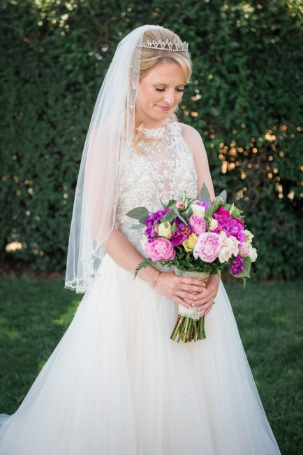 A blond, young bride glances down at a purple and pink bouquet.