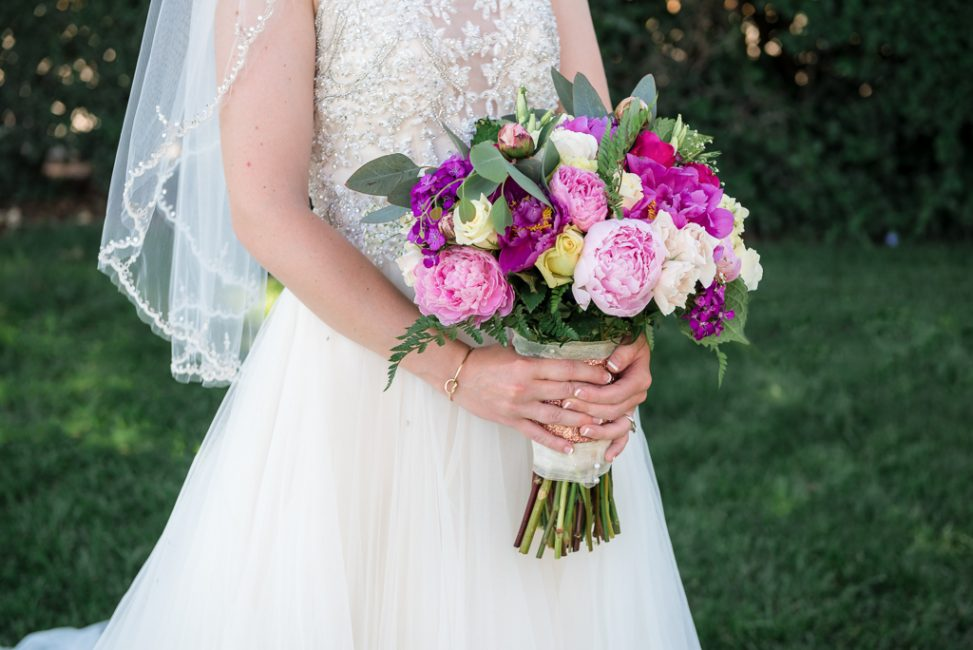 Detail shot of a bride holding a pink and purple wedding bouquet.