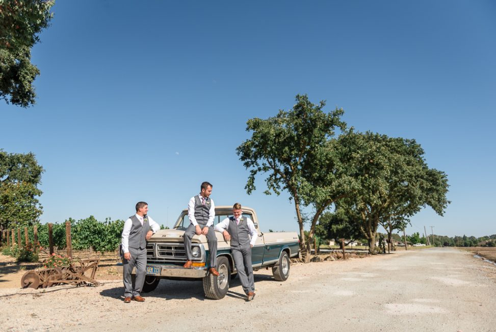 A groom and his groomsmen pose seated an old Ford truck.