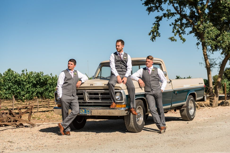 Close up photo of a groom and his groomsmen resting on a Ford truck.