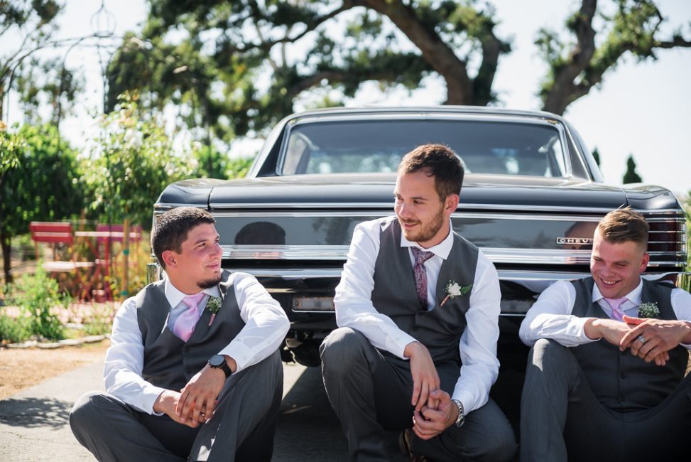 Groomsmen enjoy some downtime by a vintage muscle car.