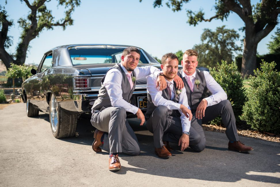 A groom and his guys pose behind a Chevy muscle car.
