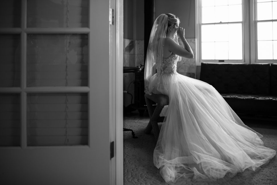 A bride tears up while sitting alone before her wedding ceremony.