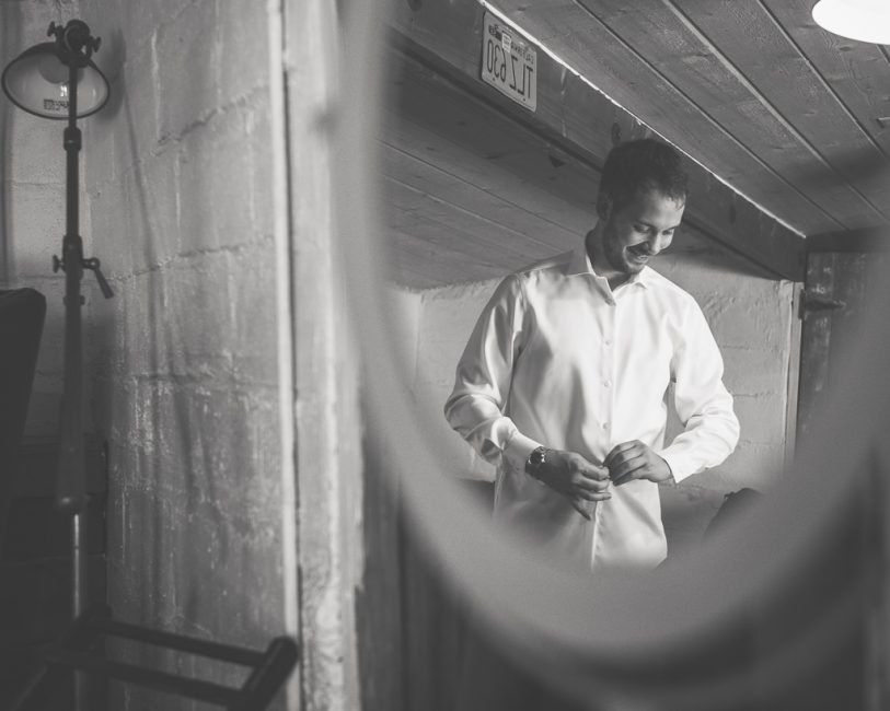 A groom dresses in preparation for his wedding day.