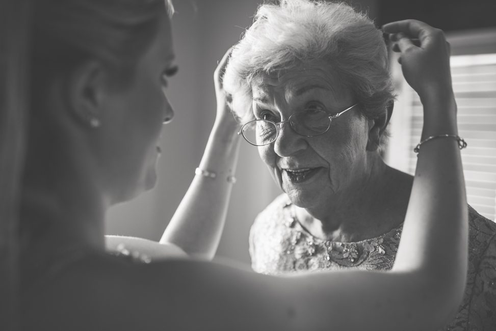 A bride places a tiara upon her grandmother's head.