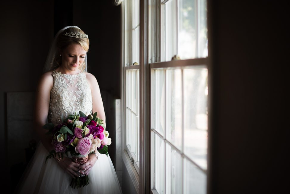 A bride waits by a window as her wedding ceremony is about to begin.