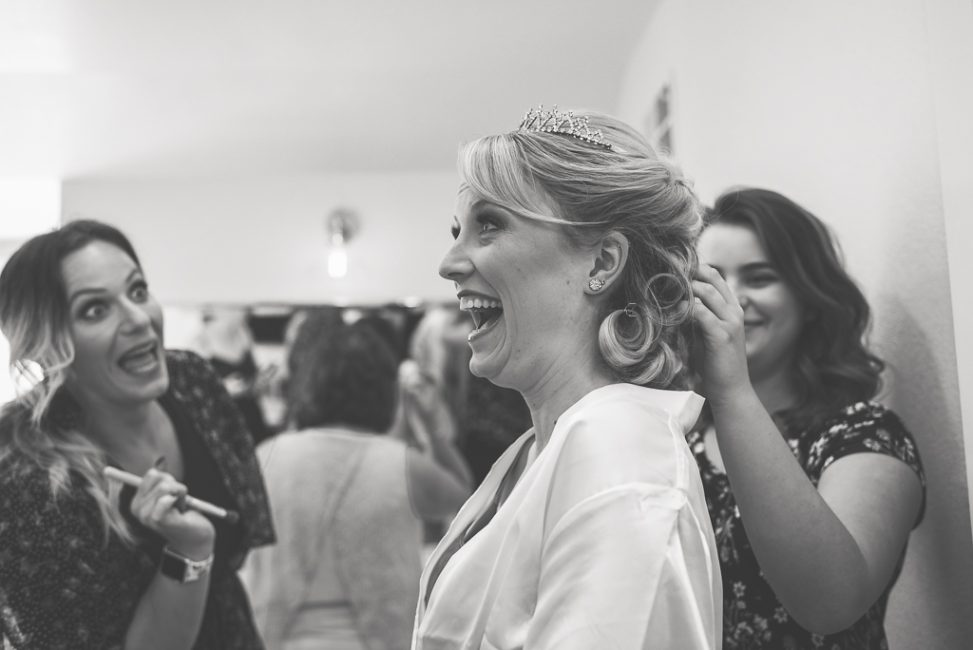 A makeup artist shares a joke with a bride as they prepare for the ceremony