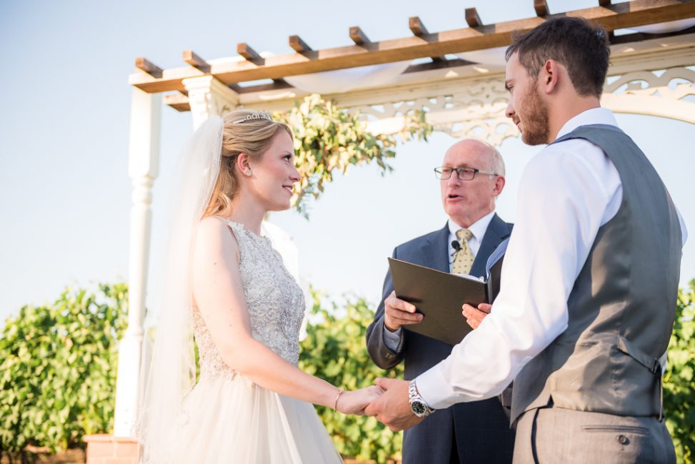 A bride and groom listen as an officiant explains the meaning of marriage.
