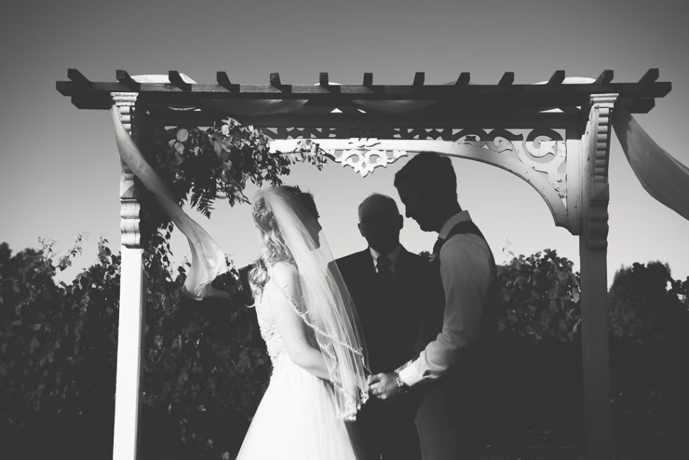 A bride and groom pray with an officiant underneath a trellis at their wedding ceremony.