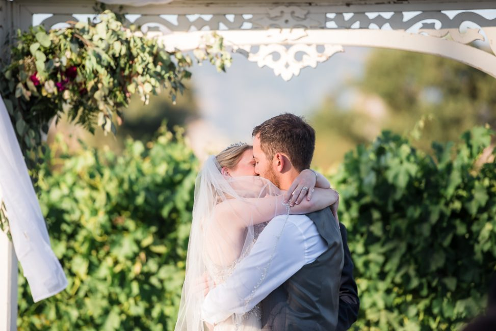 A bride and groom embrace for their kiss at a wedding ceremony.