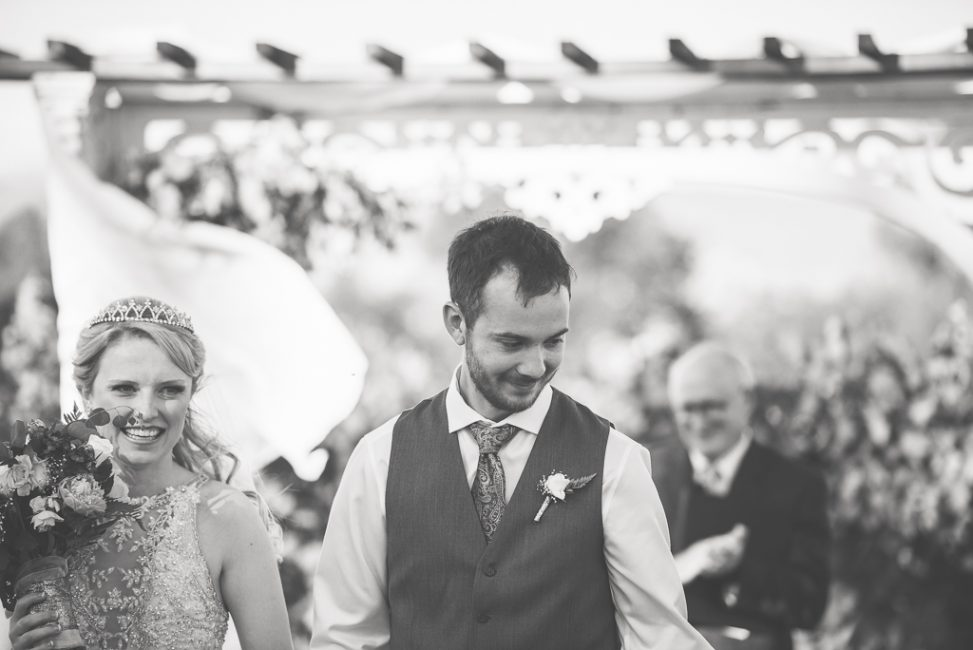 An ecstatic bride and groom walk away from the altar at their wedding.
