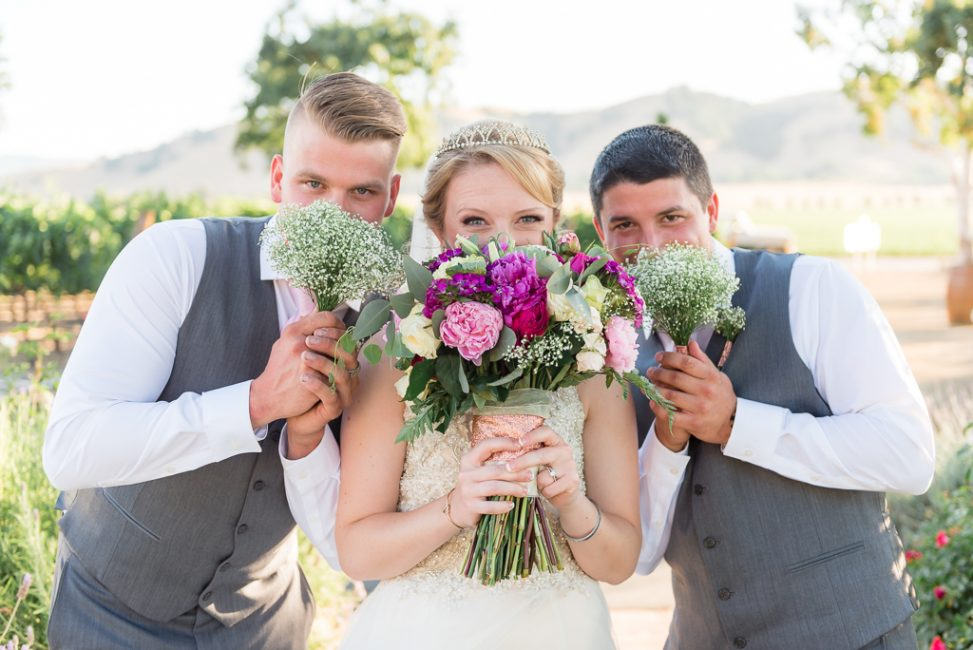 A bride and groomsmen pose behind bouquets.
