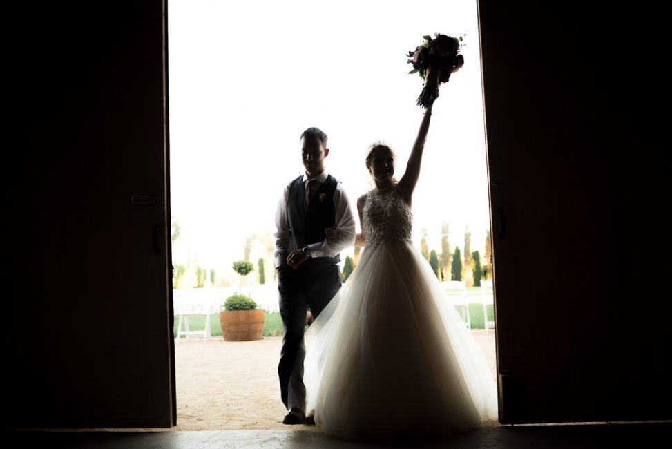 Silhouette of a bride and groom entering their wedding reception.