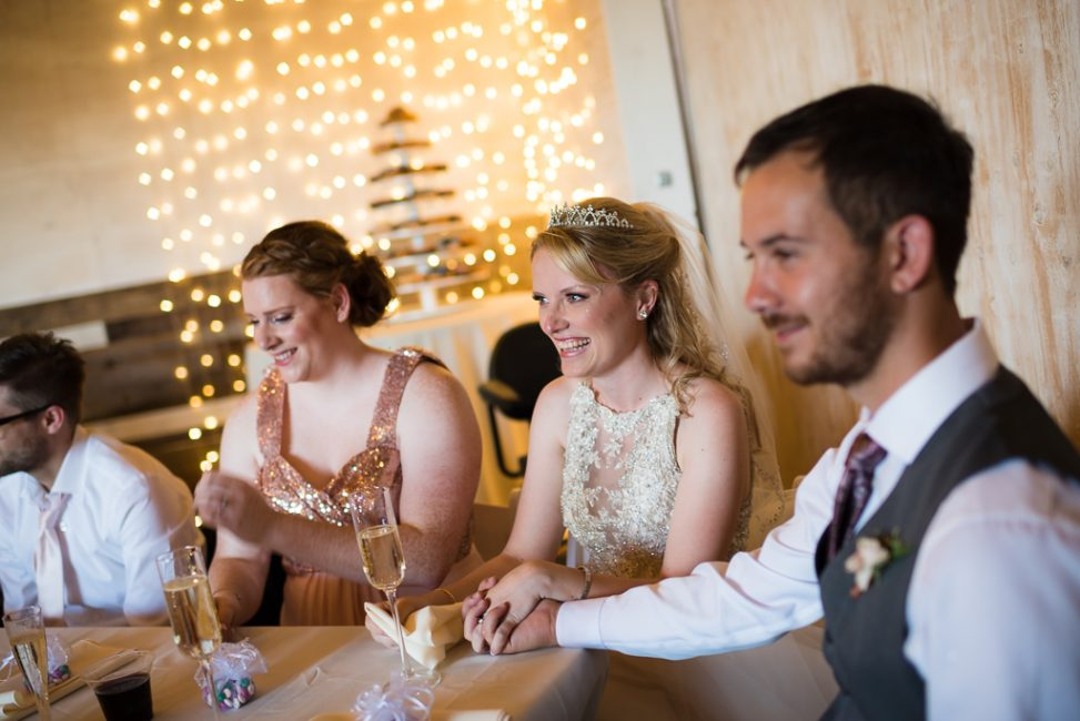 Newlywed husband and wife enjoy listening to a speech at their reception.