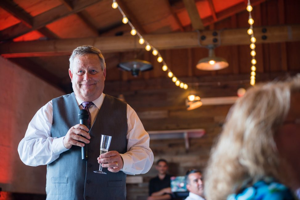 A father toasts his daughter and son-in-law's marriage inside the barn at the Fitz Place.
