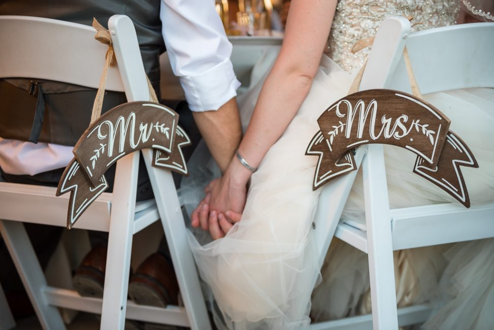 Detail image of a Mr. and Mrs. sign hanging behind a bride and groom at their wedding reception.