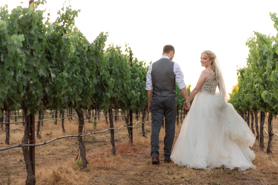 A bride glances back while walking along a vineyard with her new husband.