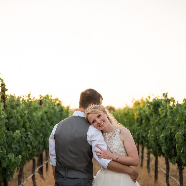 A bride and groom embrace in the middle of a vineyard row.