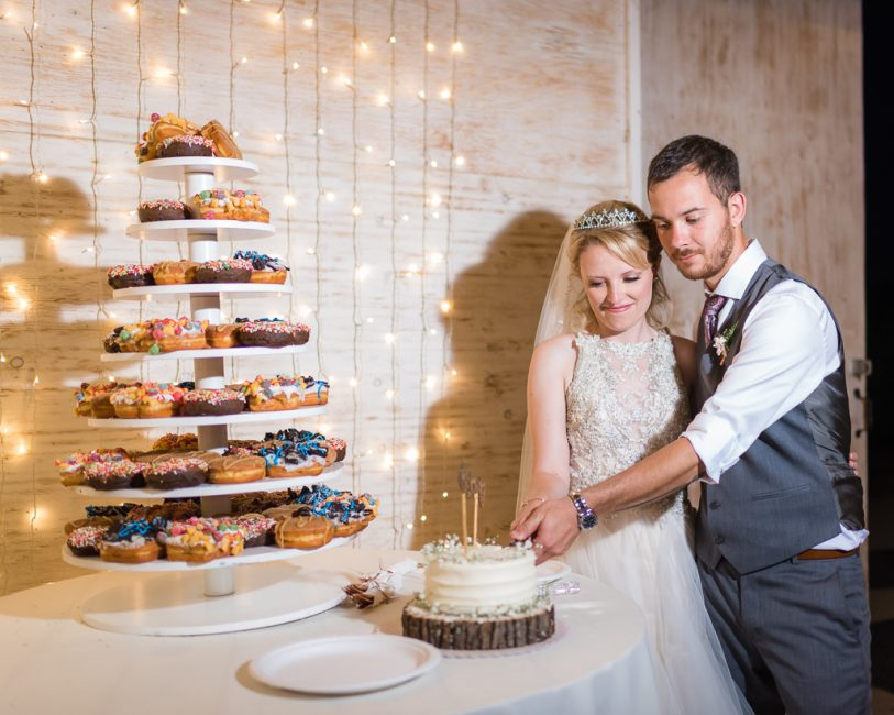 A bride and groom slice their first slice of cake at the wedding reception.