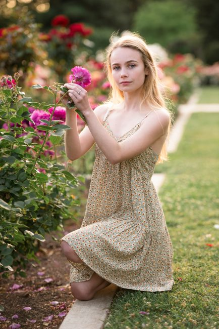 Photograph of a young, blond woman kneeling near a rose bush
