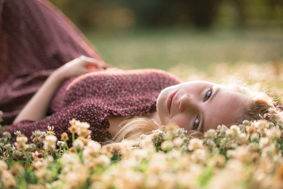 Close up portrait of young woman laying in the grass