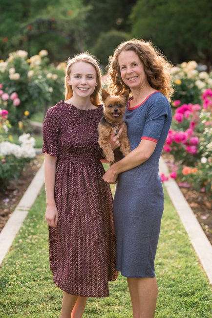 A young woman poses with her mother and puppy in a rose garden.