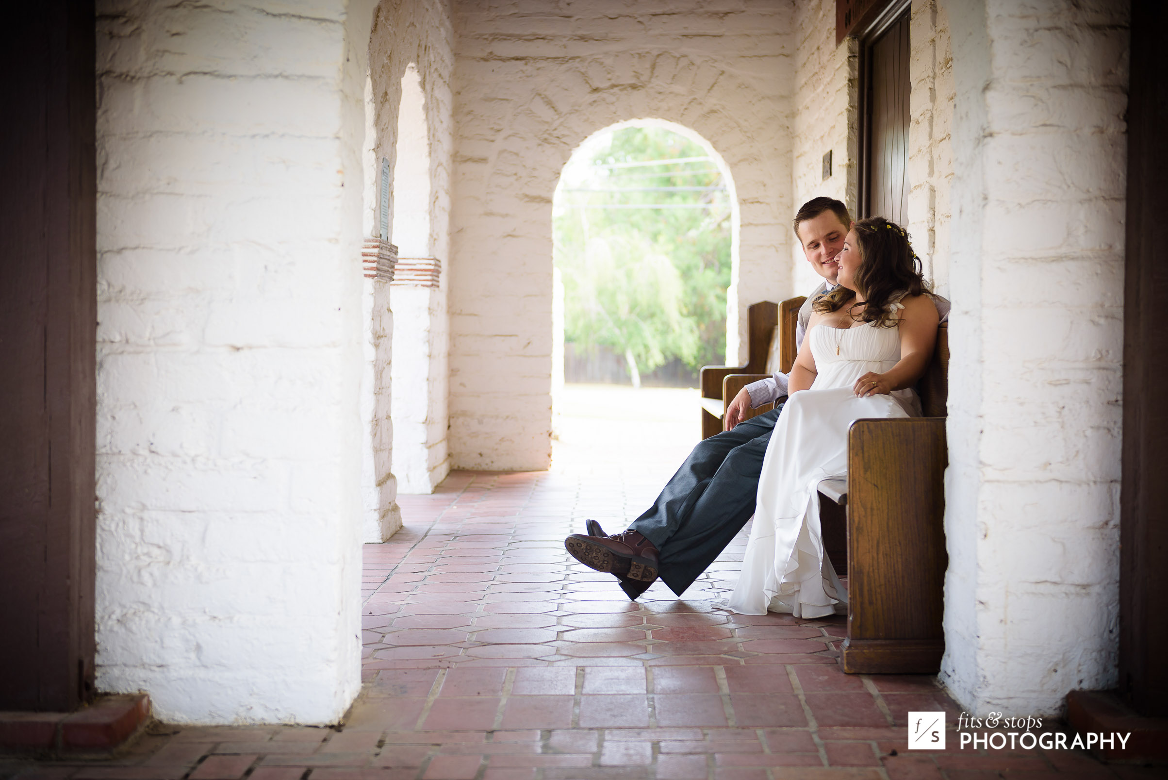 A newlywed couple sit upon a pew with an archway at Carmichael Presbyterian Church