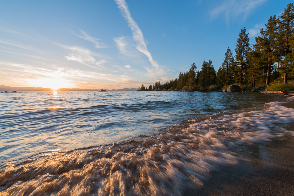 The waves breaking on a quiet beach in South Lake Tahoe at sunset.