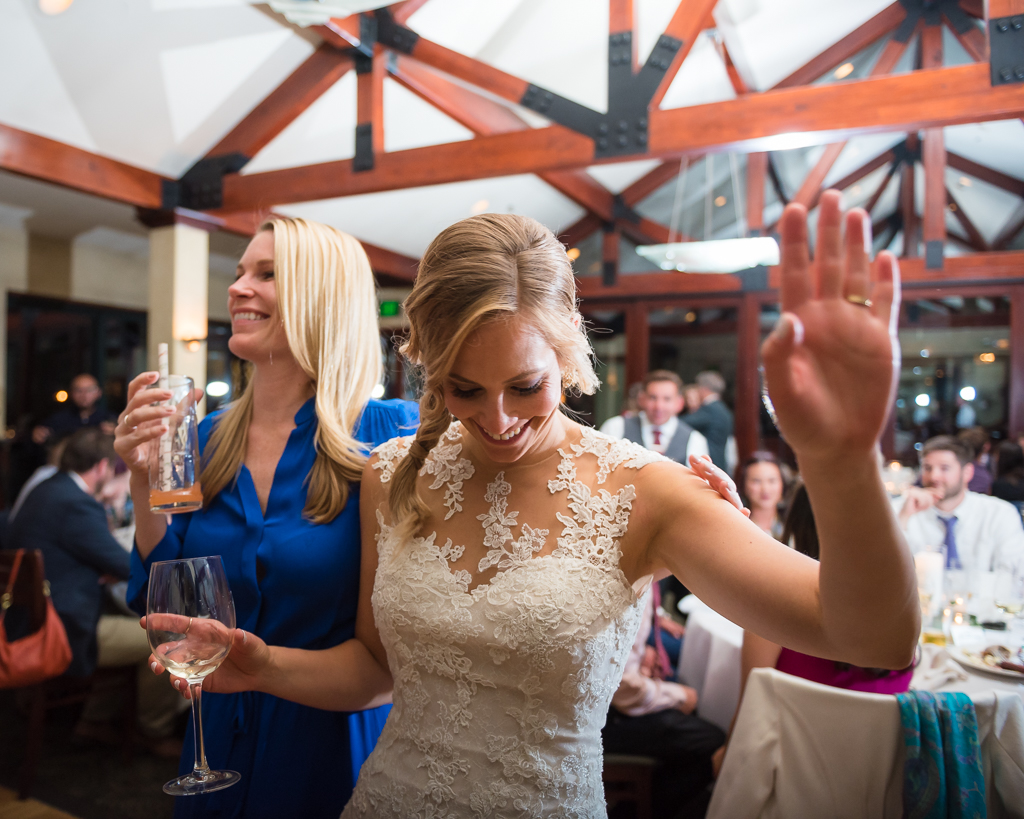 A bride dances enthusiastically at her wedding reception.