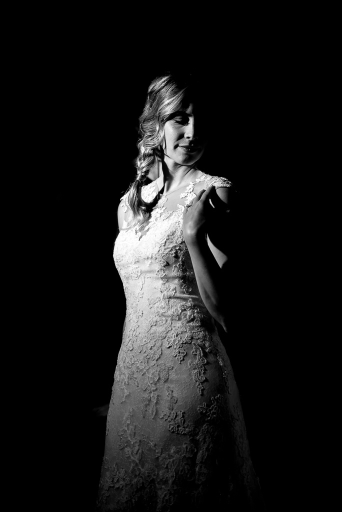 A moody, high-key portrait of a bride in her wedding dress.