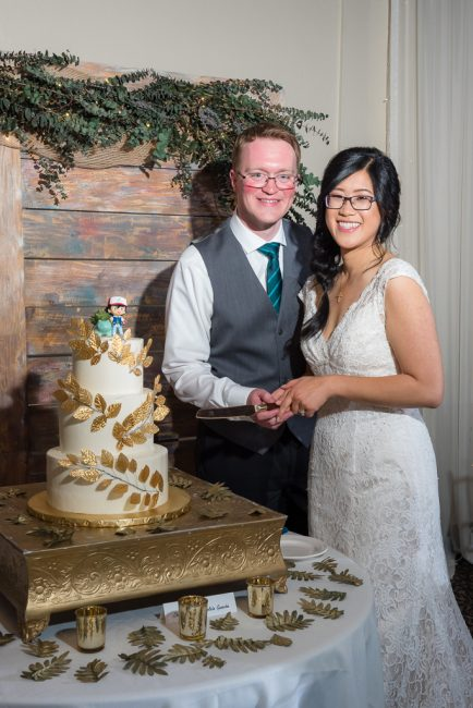 A bride and groom smile as they prepare to cut their gamer's wedding cake
