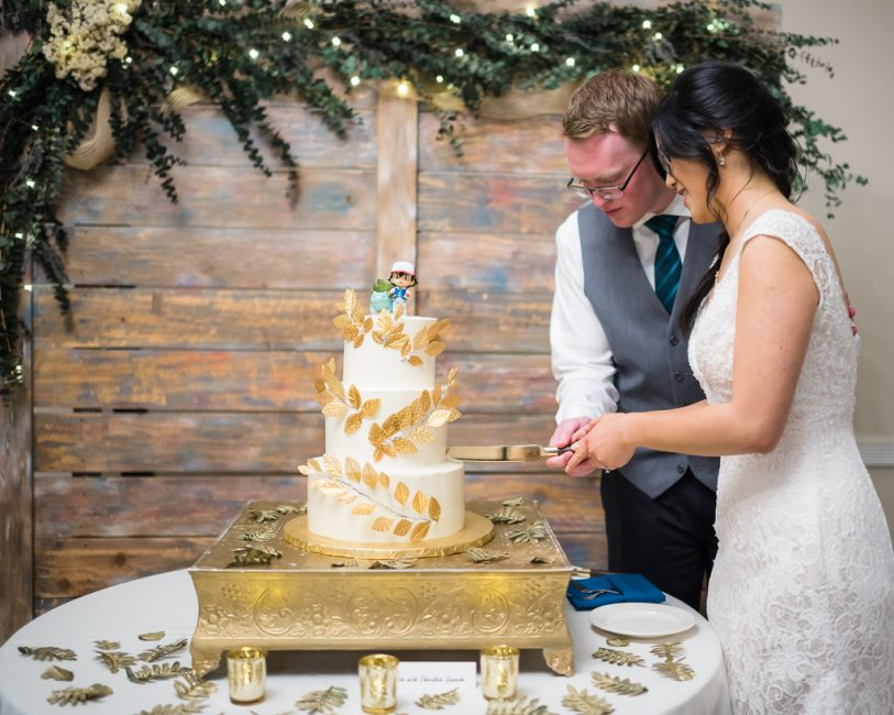Cutting a wedding cake with pokemon cake topper