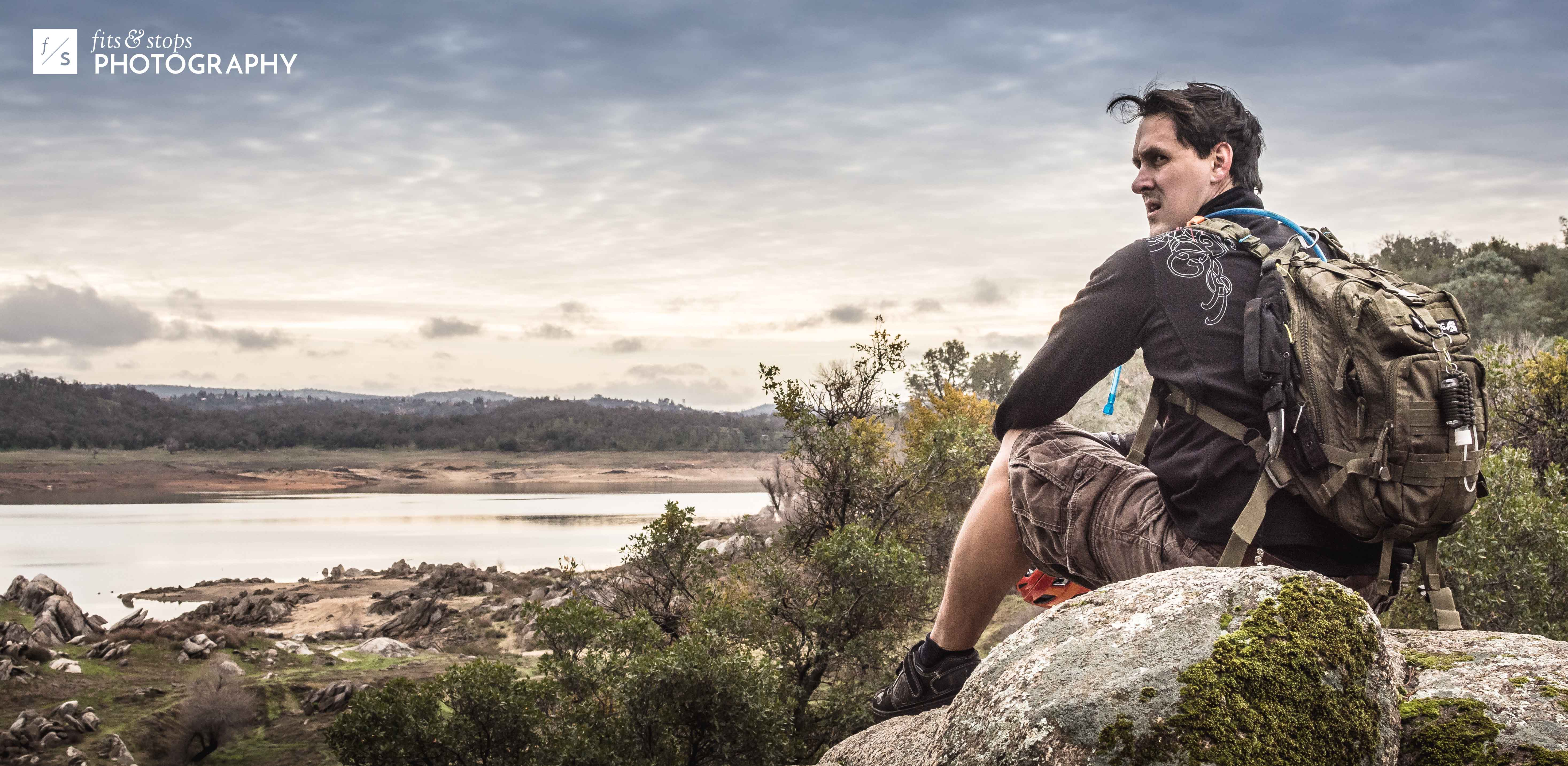 A high-clarity photograph of a mountain biker taking a break on a rock, overlooking the landscape of Doton's Cove at Folsom Lake in Northern California.