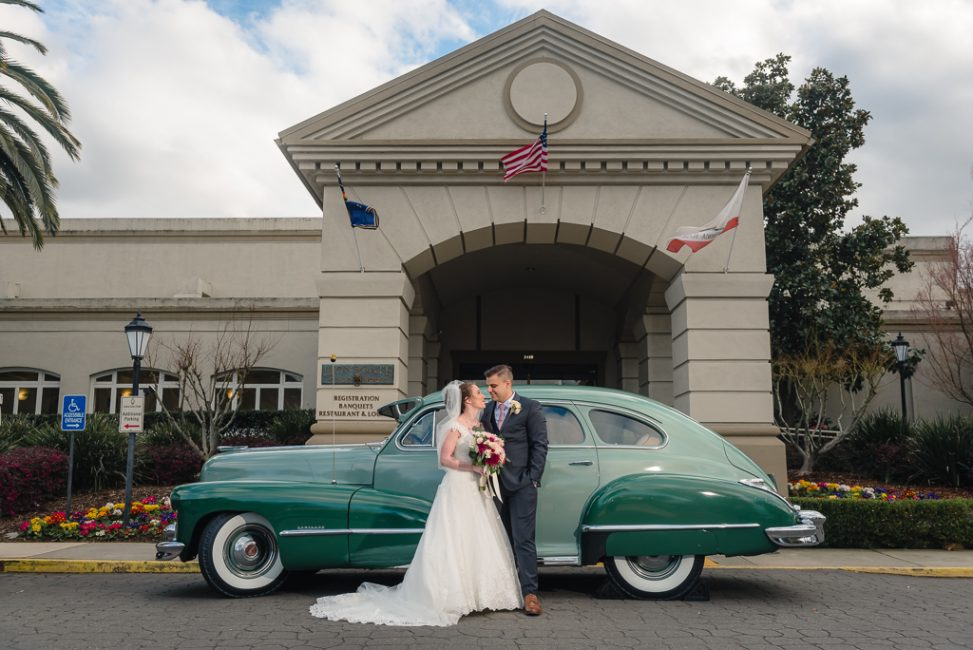 A newlywed bride and groom cuddle outside the entrance to the Officer's Club with a vintage Cadillac