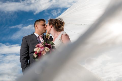 A groom kisses his bride on the nose as her veil waves in the foreground