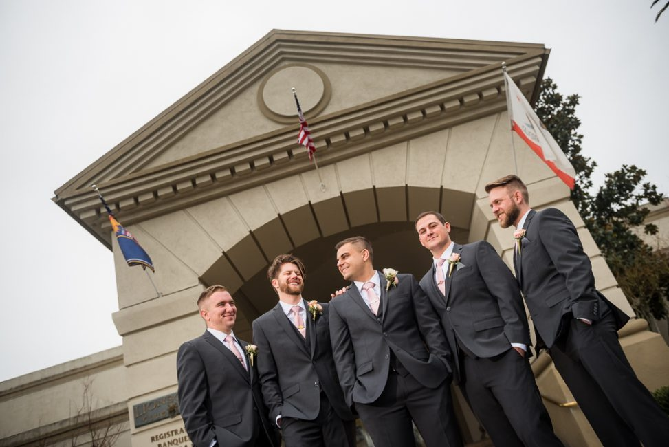 A group of groomsmen pose outside the entrance to the Officer's Club