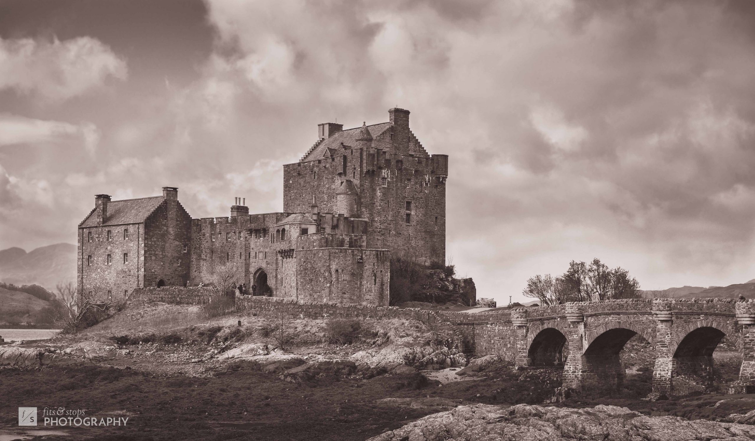 A moody, sepia-toned landscape photograph of Eilean Donan Castle, seated at the crossing of Loch Duich, Loch Alsh and Loch Long.