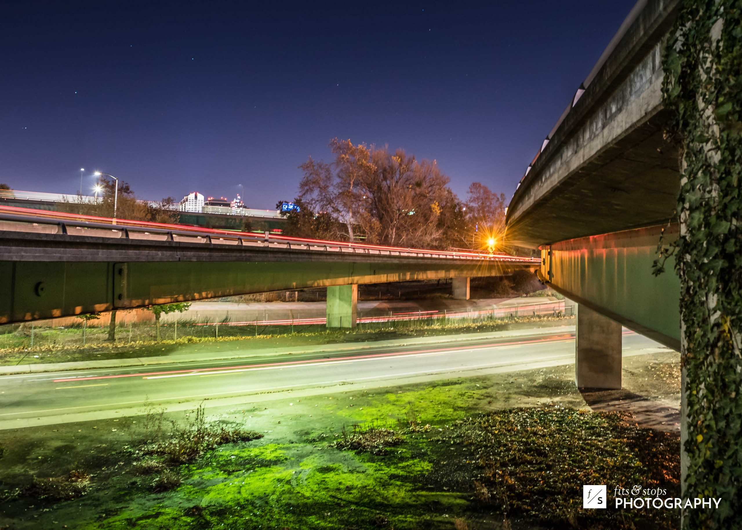 A long-exposure photograph taken between the elevated highways of downtown Sacramento, California at nighttime.